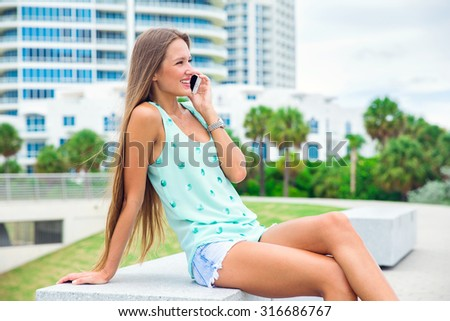 beautiful girl with long hair talking on the mobile phone - stock photo