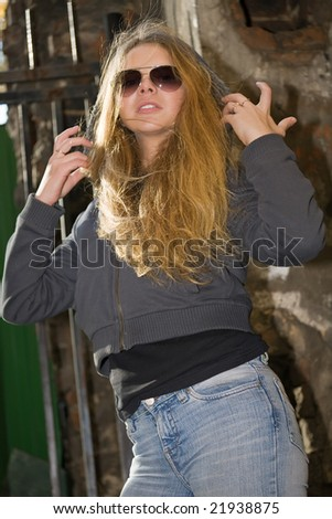 beautiful girl with long hairs puts the hood on - stock photo