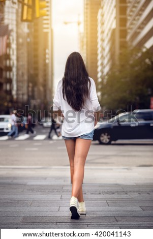 Beautiful girl with long legs walking around New York City street wearing jeans shorts. Rear view. - stock photo