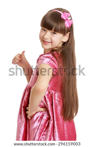 Beautiful girl with long, lush hair and short bangs in pink velvet dress shows the gesture of thumb is all right , or hitchhiking , close-up - isolated on white background - stock photo