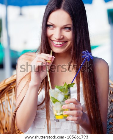 Beautiful girl with mojito drink in cafe - stock photo