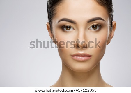 Beautiful girl with nice make-up and ponytail looking at camera. Beauty portrait, closeup, full face. Indoor, studio, gray background - stock photo