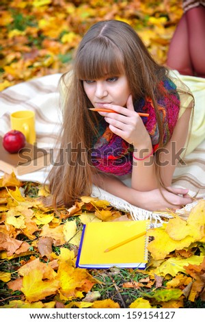 Beautiful girl with notebook on a background autumn leaves - stock photo