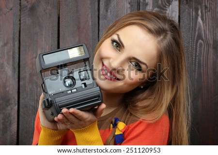 beautiful girl with old retro camera in his hands on the wooden background - stock photo