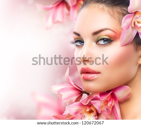 Beautiful Girl With Orchid Flowers.Beauty Model Woman Face. Perfect Skin. Professional Make-up.Makeup. Fashion Art - stock photo