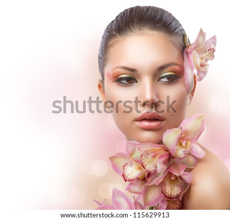 Beautiful Girl With Orchid Flowers.Beauty Woman Face. Perfect Skin. Professional Make-up.Makeup - stock photo