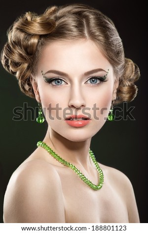 Beautiful girl with perfect skin and bright makeup. portrait shot in the studio on a green background. - stock photo