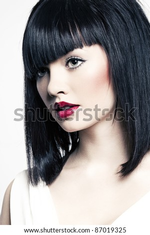 beautiful girl with perfect skin and bright red lipstick, black straight hair on a white background - stock photo