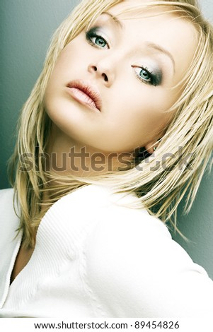 beautiful girl with perfect skin, blond hair and blue eyes in white sweater against a dark background - stock photo