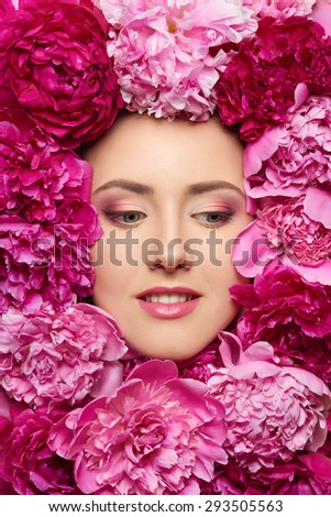 Beautiful girl with pink peony flowers. Closeup of beauty model woman face with perfect skin and professional makeup looking to the side  - stock photo