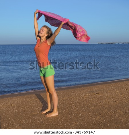 Beautiful girl with pink scarf on the beach. Travel and Vacation. - stock photo