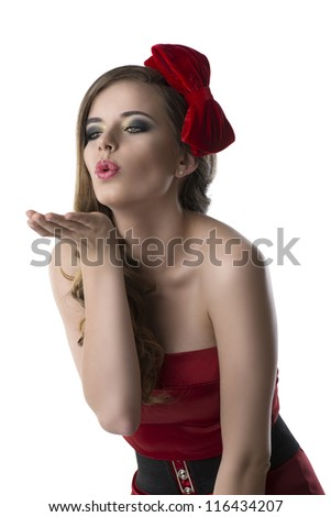 beautiful girl with red and elegant dress and one bow in the hair, she is turned of three quarters at right and sends one kis with one hand - stock photo