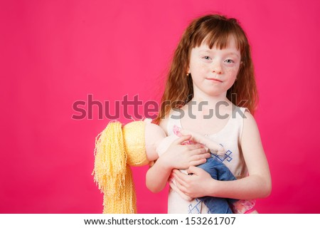 beautiful girl with red hair holding a doll. mimics mom - stock photo