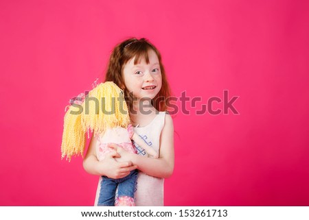 beautiful girl with red hair hugging her doll and smiling - stock photo