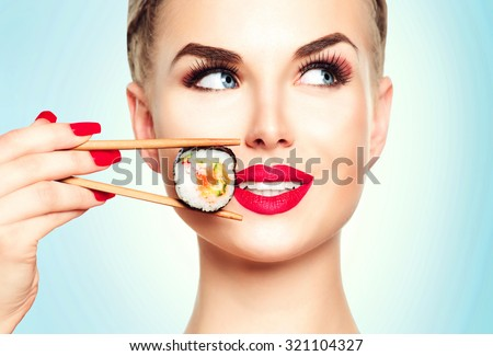 Beautiful girl with red lips and manicure eating sushi close-up. Smiled woman with perfect make up holding Sushi roll with chopsticks. Healthy Japanese food. Diet concept - stock photo