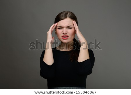 Beautiful girl with red lips holding her hands behind her head. She is in pain or frustration - stock photo