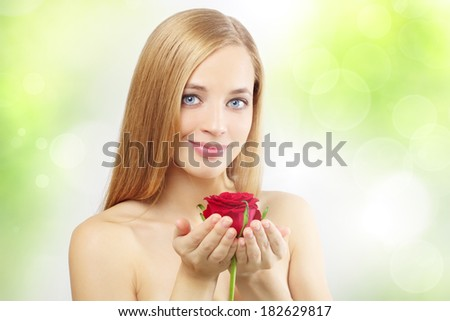 beautiful girl with red rose on a green background - stock photo