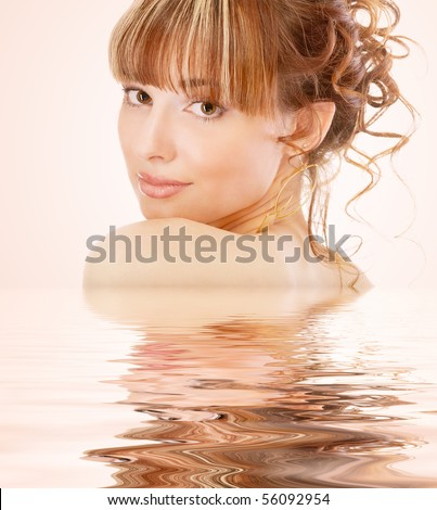 Beautiful girl with reflection in water, on pink background. - stock photo