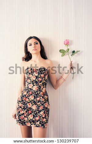 beautiful girl with rose on background wall - stock photo
