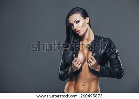 Beautiful girl with sexy breasts in unbuttoned jacket with long black hair. - stock photo