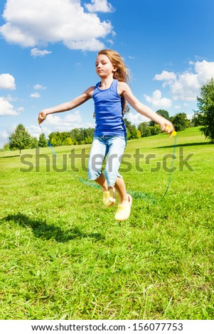 Beautiful girl with skipping rope jumping in the park on green grass field on sunny summer day - stock photo