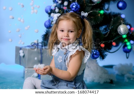beautiful girl  with snow near a Christmas fir-tree - stock photo