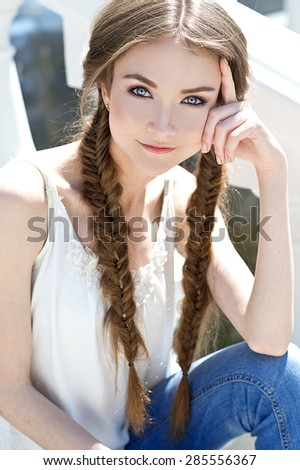 Beautiful girl with stylish braid. Young pretty woman summer outdoor portrait.  - stock photo