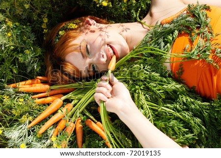Beautiful girl with tasty carrot and flowers - stock photo