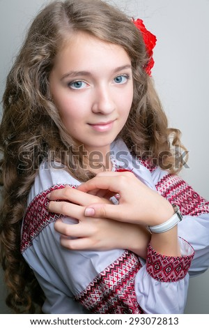 Beautiful girl with Ukrainian embroidery and long hair, with a poppy in her hair   - stock photo