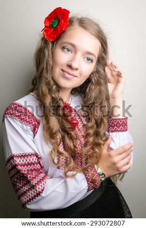 Beautiful girl with Ukrainian embroidery and long hair, with a poppy straightens hair - stock photo