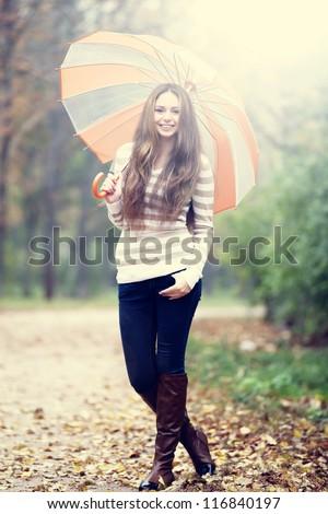 Beautiful girl with umbrella at autumn park. - stock photo