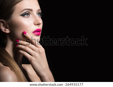 Beautiful girl with unusual black arrows on eyes and pink lips and nails. Beauty face. Picture taken in the studio on a black background. - stock photo