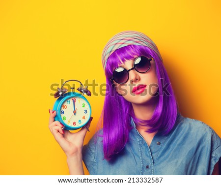 Beautiful girl with violet hair in sunglasses and alarm clock on yellow background. - stock photo