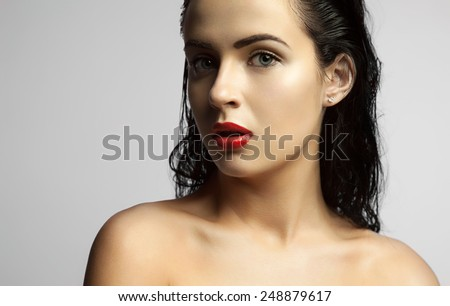 Beautiful girl with wet skin and long wet hair. Portrait models with bronze skin and red lips. Brunette with blue eyes on a gray background. - stock photo