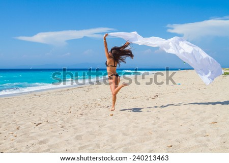 Beautiful Girl With White fabric on The Beach. Travel and Vacation. Freedom Concept. - stock photo