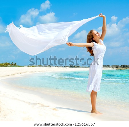 Beautiful Girl With White Scarf Jumping on The Beach. Travel and Vacation. Freedom Concept. Full length portrait - stock photo