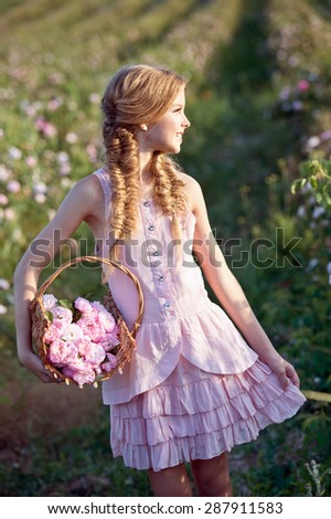 Beautiful girl with wreath of roses on nature on sunset - stock photo