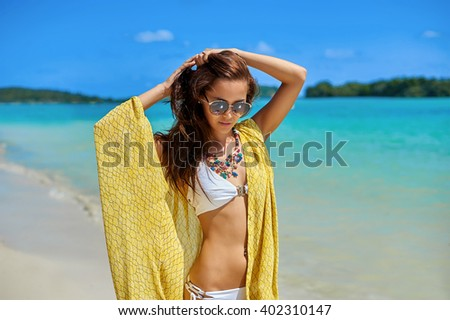 Beautiful girl with yellow pareo having fun on the beach - stock photo