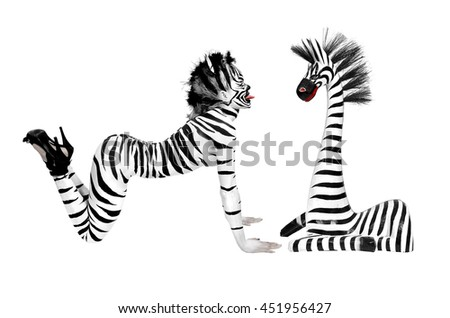 beautiful girl with zebra body paint sticking out his tongue to a zebra wood - stock photo