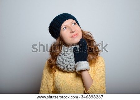 beautiful girl wondering about the wonderful, life-style of winter clothes studio photo isolated on a gray background - stock photo