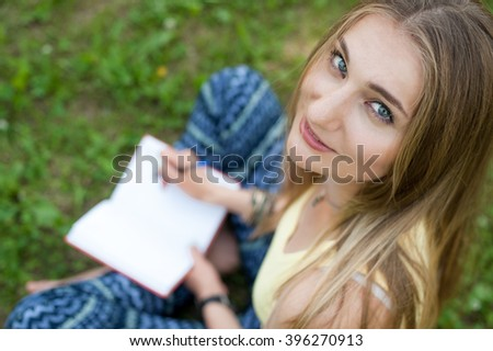 Beautiful girl writes in his diary in the park - stock photo