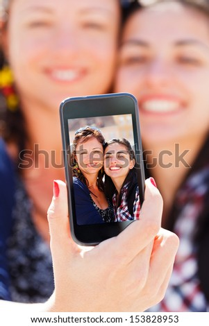 Beautiful girlfriends taking a self shot with phone. - stock photo