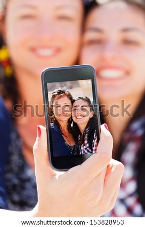 Beautiful girlfriends taking a self shot with phone. - stock photo