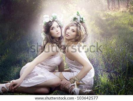 Beautiful girls are illuminated by sun rays. - stock photo