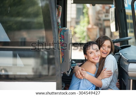 Beautiful girls are sitting on doorsteps of a bus and embracing. They are looking at the camera and smiling. Copy space in left side - stock photo