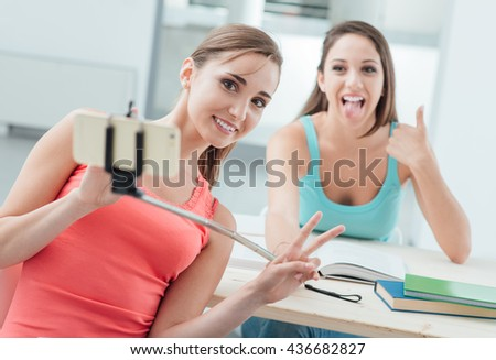 Beautiful girls at school having fun and taking selfies with a selfie stick and a mobile phone - stock photo
