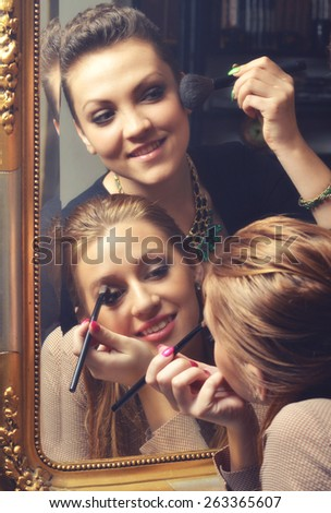 Beautiful girls having fun while putting make up in front of the old mirror. - stock photo