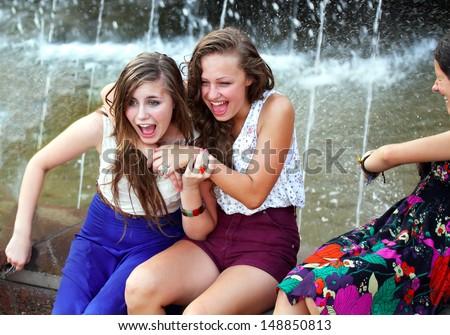 Beautiful girls having fun with a fountain. - stock photo