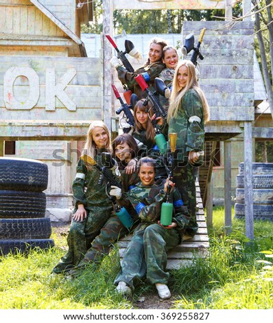 Beautiful girls in military uniform with paintball guns - stock photo