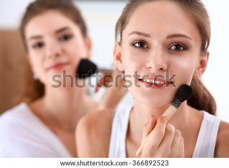 Beautiful girls looking in the mirror and applying cosmetic with a big brush - stock photo